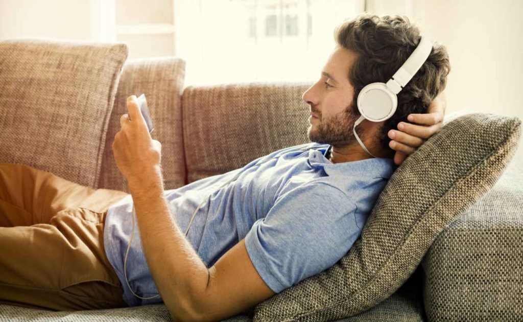 Man watching a video on his phone with headphones on the couch