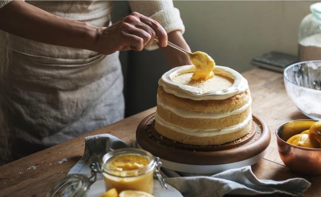 Hand placing lemon curd on a cake