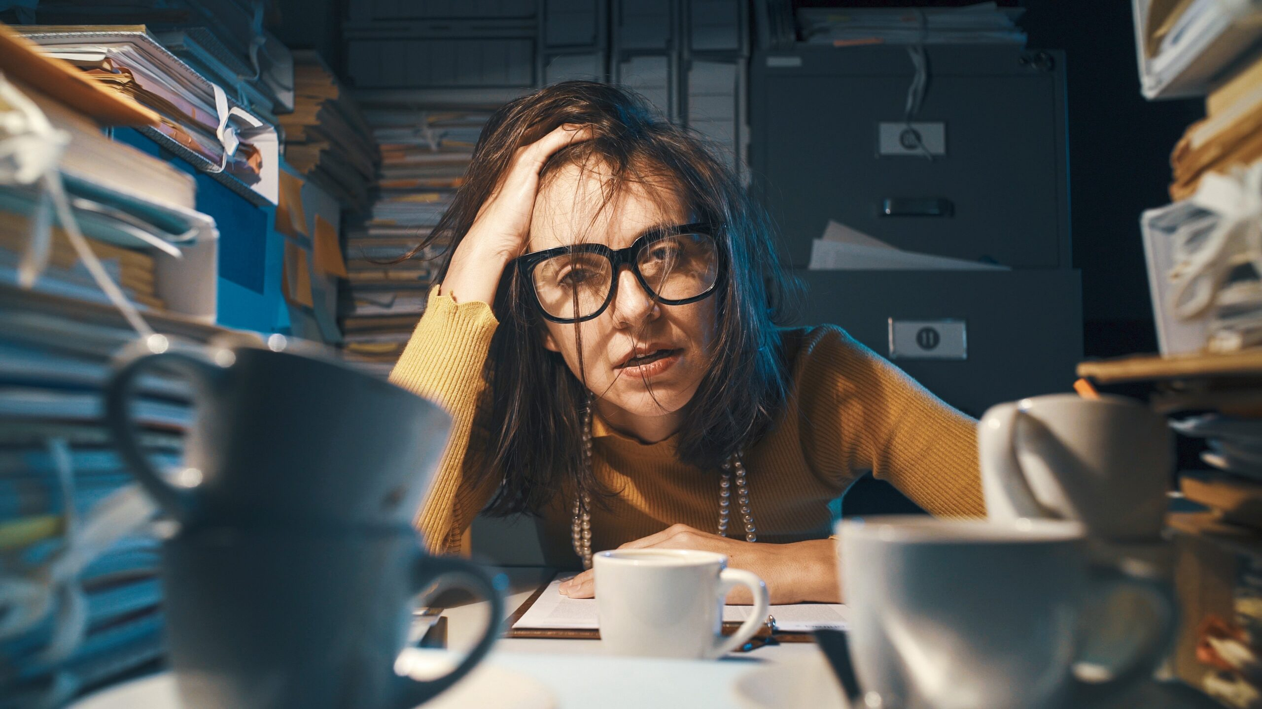 stress photo woman at desk full of papers scaled